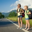 Stock Photo: Two girls with backpacks walking on road