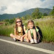 Two girls with backpacks sitting on the road — Stock Photo