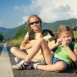Stock Photo: Two girls with backpacks sitting on road