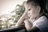 Porträtt av en ledsen tjej som sitter nära fönstret — Stockfoto