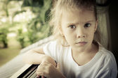 Portrait of a sad girl sitting near the window — Stock Photo
