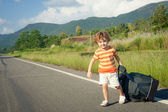 Little boy with a big bag goes on the road in the daytime — Stock Photo