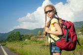 One girl with backpack walking on the road — Stock Photo