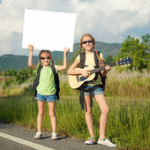Two girls with backpacks standing on roadside of the road — Stock Photo