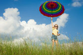 Girl jumping on the road with an umbrella in his hand — Stockfoto