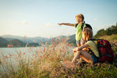 Two little girls watching the sunset on the lake — Stock Photo