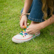 White sneakers on girl legs on grass during sunny serene summer — Stock Photo
