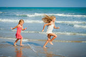 Happy kids playing at the beach — Stock Photo