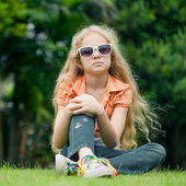 Teen girl in the park sitting on the grass. — Foto de Stock