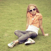 Teen girl in the park sitting on the grass. — 图库照片