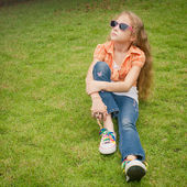 Teen girl in the park sitting on the grass. — Foto Stock