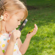 One little girl with magnifying glass outdoors in day time — Stock Photo #36966495