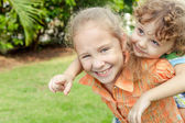 Two happy little kids playing in the garden — Stockfoto