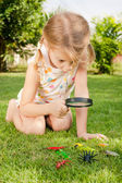 One little girl with magnifying glass outdoors in the day time — Stock Photo