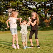 Drie gelukkige kleine kinderen spelen in het park in de dagtijd — Stockfoto