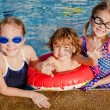 Two little girls and little boy playing in the pool — Stock Photo