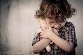 Sad little boy hugging a doll — Stock Photo