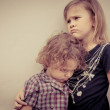 Portrait of sad little girl and little boy standing near wall in — Stock Photo
