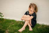Portrait of sad little girl sitting near  wall in the day time — Stock Photo
