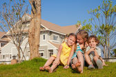 Two happy  girls and little boy sitting near the house — Stock Photo