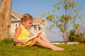 Little girl sitting and reading a book on nature — Stock Photo