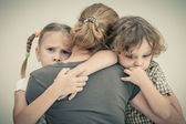 Sad children hugging his mother — Stock Photo