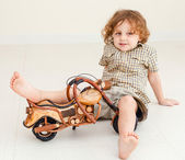 Little boy sitting on the floor and playing toy motorcycle — Stock Photo