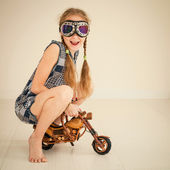 Little girl in glasses on toy motorcycle — Stock Photo