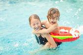Due ragazzini, giocando in piscina — Foto Stock