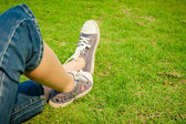 Youth sneakers on girl legs on grass during sunny serene summer  — Stock Photo