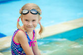 Little girl sitting near swimming pool — ストック写真