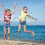 Happy little girls jumping on beach — Stock Photo #47203679