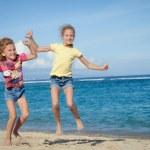 Happy little girls jumping on beach — Stock Photo #47203875