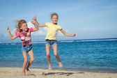 Happy little girls jumping on beach — Stock Photo