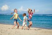 Happy kids playing on beach — Stock Photo