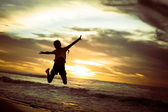 Happy girl jumping on the beach on the dawn time — Stock fotografie