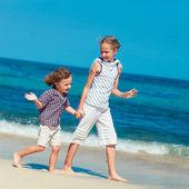 Niños felices jugando en la playa durante el día — Foto de Stock