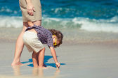 Mother and  son playing on the beach in day time — Stock Photo