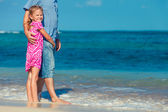 Father and daughter standing on the beach in the day time — Stock Photo