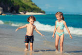 Two little kids playing at the beach in the day time — Stock Photo