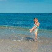 Little girl running on the beach in the day time — Stock Photo
