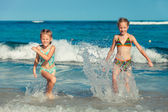 Two sisters splashing on the beach in the day time — Stock Photo