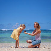 Mother and daughter playing at the beach in the day time — Stock Photo