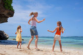 Happy family jumping at the beach in the day time — Stockfoto