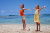 Happy little girls standing at the beach in the day time — Stock Photo