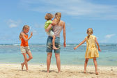 Happy family playing at the beach in the day time — Stock Photo