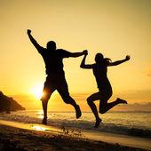 Mutlu bir aile sahilde şafak zamanda atlama — Stok fotoğraf