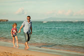 Father and daughter walking on the beach at the day time — Stock Photo