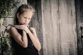 Ritratto di bambina triste in piedi vicino a muro in pietra nel giorno — Foto Stock