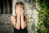 Portrait of sad little girl standing near stone wall in the day — Stock Photo
